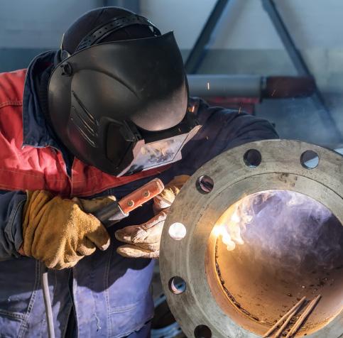 Man welding a flange onto a steel pipe